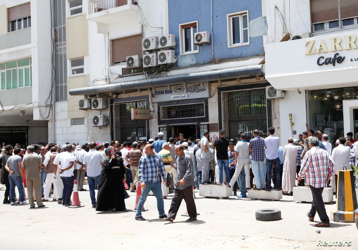 People queue to withdraw money at a bank in Tripoli, Libya, May 25, 2016.