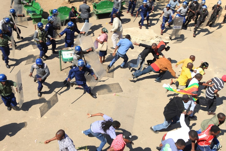 Zimbabwe Protests: Zimbabwean riot police clash with protestors during a demonstration against the introduction of bond notes by the Reserve Bank of Zimbabwe, in Harare, Wednesday, Aug. 17, 2016.