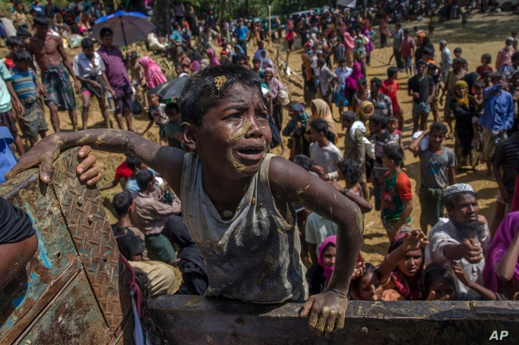 A Rohingya Muslim boy, who crossed over from Myanmar into Bangladesh, pleads with aid workers to give him a bag of rice near Balukhali refugee camp, Bangladesh, Thursday, Sept. 21, 2017.