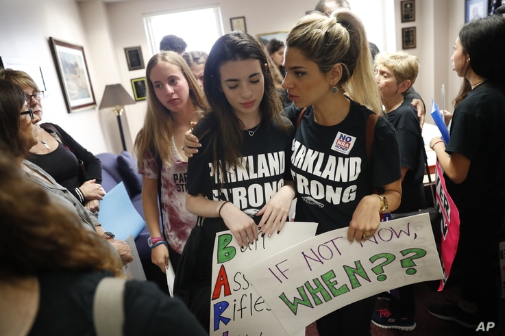 Lital Donner, youth director for Congregation Kol Tikvah, comforts Aria Siccone, 14, a 9th grade student survivor from Marjory Stoneman Douglas High School, where over a dozen were killed in a mass shooting on Wednesday.