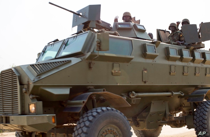 FILE - Soldiers from the Uganda People's Defense Force (UPDF) are seen driving in an armored vehicle through the streets of Bor, Jonglei State, South Sudan, Jan. 19, 2014.