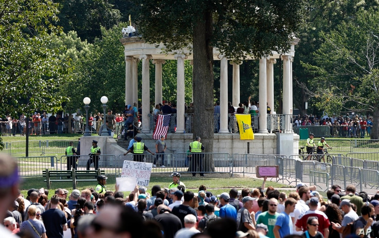 """Organizers stand on the bandstand on Boston Common during a """"free speech"""" rally staged by conservative activists, in Boston, Aug. 19, 2017. Counterprotesters stand along barricades ringing the bandstand."""