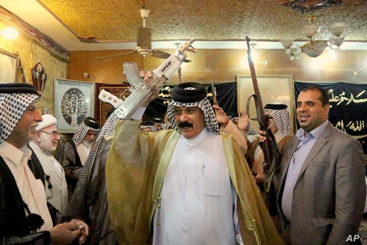 Iraqi Shiite tribal leaders chant slogans against the al-Qaida-inspired Islamic State of Iraq and the Levant (ISIL), in Baghdad, Iraq, Friday, June. 13, 2014. The tribal leaders met in Sadr city on Friday and declared their readiness along with their...