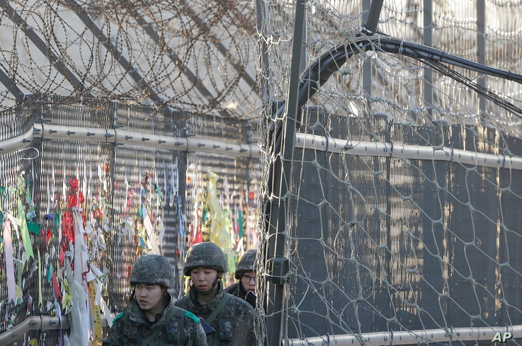 South Korean Army soldiers patrol by ribbons, wishing for the reunification of the two Koreas, attached on the barbed-wire fence in Paju, near the border with North Korea, South Korea, Feb. 7, 2016.
