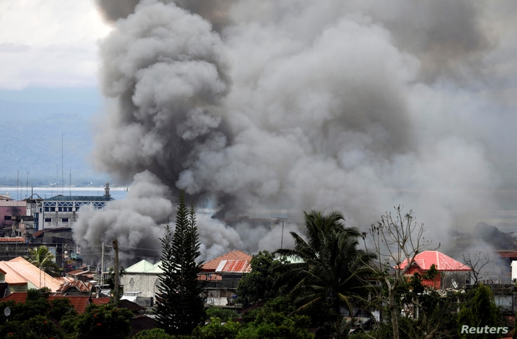 FILE - Smoke rises in the residential neighborhood of Marawi City as fighting rages between government soldiers and the Maute militant group, in southern Philippines, May 27, 2017.