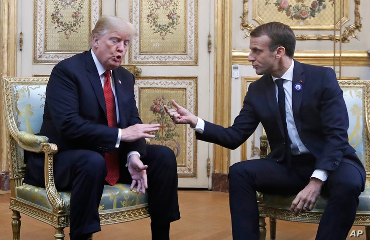 President Donald Trump and French President Emmanuel Macron gesture during their meeting inside the Elysee Palace in Paris, Nov. 10, 2018.