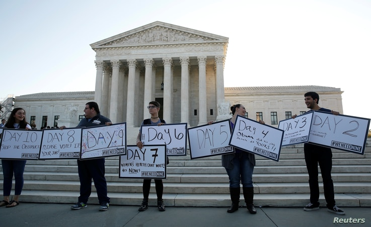 Protesters with We Need Nine, a group calling for the U.S. Senate to allow President Barack Obama to nominate a ninth Supreme Court justice, display their signs in front of the Supreme Court in Washington, D.C., Oct. 4, 2016.