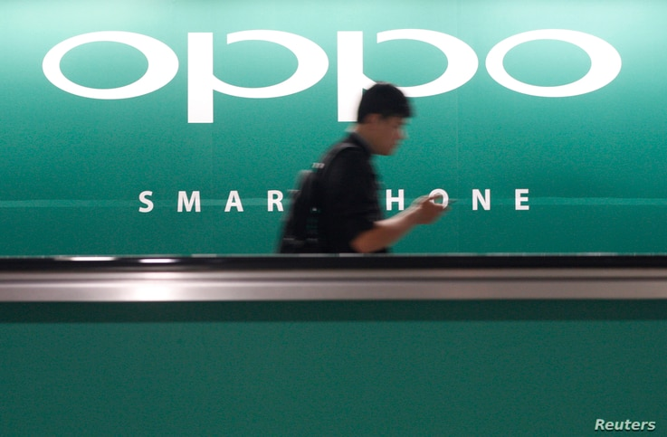 A commuter using his mobile phone passes an advertisement of Chinese smartphone maker Oppo at a train station in Singapore, May 8, 2014.