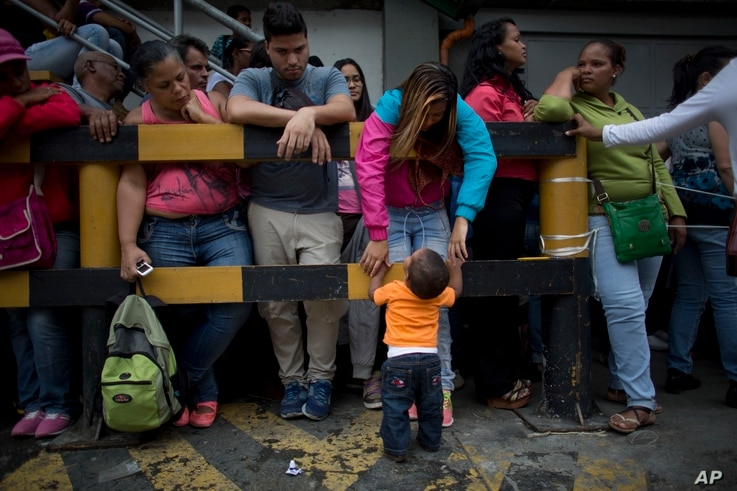 Madeley Vasquez, 16, stands with her one-year-old son Joangel outside a supermarket as she waits to buy food in Caracas, Venezuela, May 3, 2016.