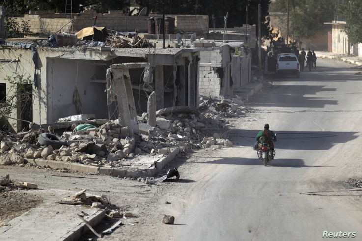 A rebel fighter rides past damaged buildings in al-Rai town, northern Aleppo countryside, Syria, Oct. 2, 2016.