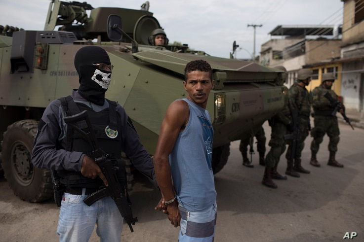 A masked police officer stands with a suspect in handcuffs, next to Brazilian marines during a surprise operation in Kelson's slum in Rio de Janeiro, Brazil, Feb. 20, 2018.
