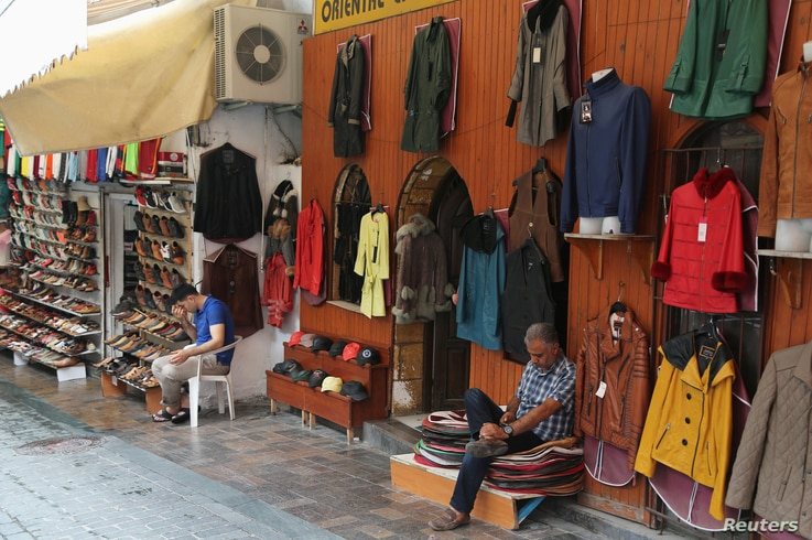 FILE - Shop vendors wait for customers in the Mediterranean resort city of Antalya, Turkey, June 3, 2016.