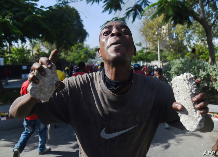A demonstrator gestures during clashes in front of the National Palace, in the center of Haitian capital Port-au-Prince, Feb. 13, 2019.