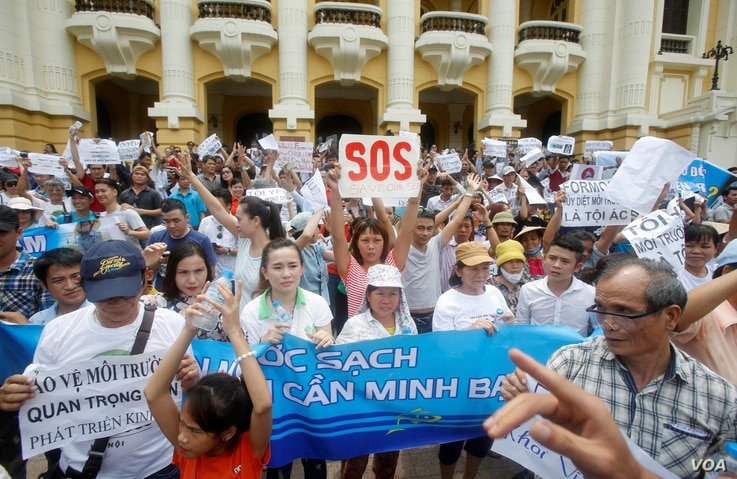 Demonstrators, holding signs to protest against Taiwanese enterprise Formosa Plastic