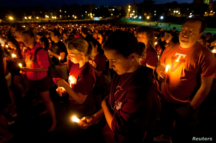 FILE - Members of the community reflect as they hold candles during a commemoration and candlelight vigil on the campus of Virginia Tech in Blacksburg, Virginia, April 16, 2012, five years after a mentally ill student gunned down 32 people at the uni...