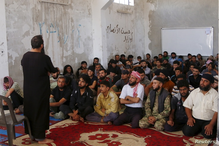 FILE - Rebel fighters from the Ahrar al-Sham Movement take Islamic and Koran lessons inside a camp, during the holy month of Ramadan in Idlib countryside, Syria, July 7, 2015. The group pulled out of a meeting of opposition groups in Saudi Arabia, De...