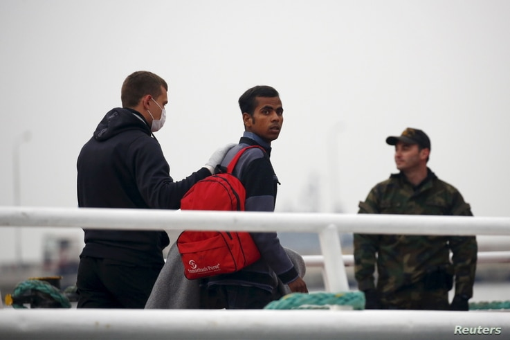 An officer (L) from European Union border agency Frontex escorts a migrant boarding a Turkish-flagged passenger boat, to be returned to Turkey, on the Greek island of Lesbos, April 8, 2016.