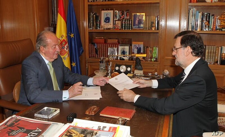 A handout photo provided on June 2, 2014 shows Spain's King Juan Carlos (L) hands over a letter of abdication to Spain's Prime Minister Mariano Rajoy at the Zarzuela Palace in Madrid.