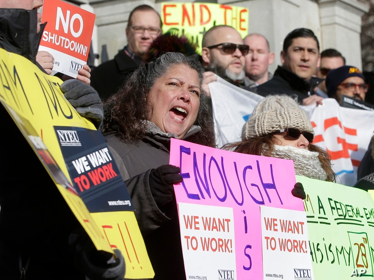 Internal Revenue Service employee Mary Maldonado, of Dracut, Mass. (C) displays a placard during a rally by federal employees and supporters, Jan. 17, 2019, in front of the Statehouse, in Boston, held to call for an end of the partial shutdown of the...