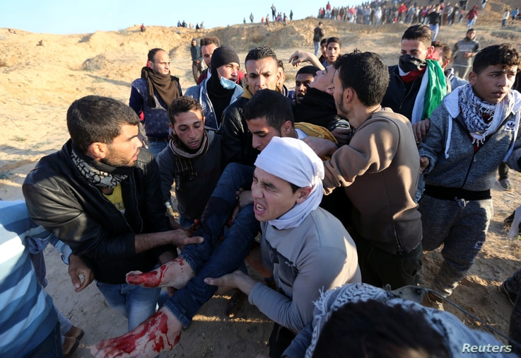 """A wounded Palestinian protester is evacuated during clashes with Israeli troops as Palestinians call for a """"day of rage"""" in response to U.S. President Donald Trump's recognition of Jerusalem as Israel's capital, near the border with Israel in the cen..."""