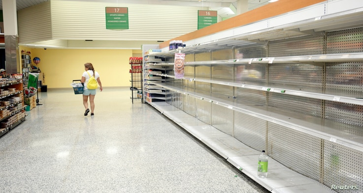 A shopper walks past empty shelves, which would normally be stocked with water, at a supermarket ahead of Hurricane Irma making landfall in Kissimmee, Fla., Sept. 9, 2017.