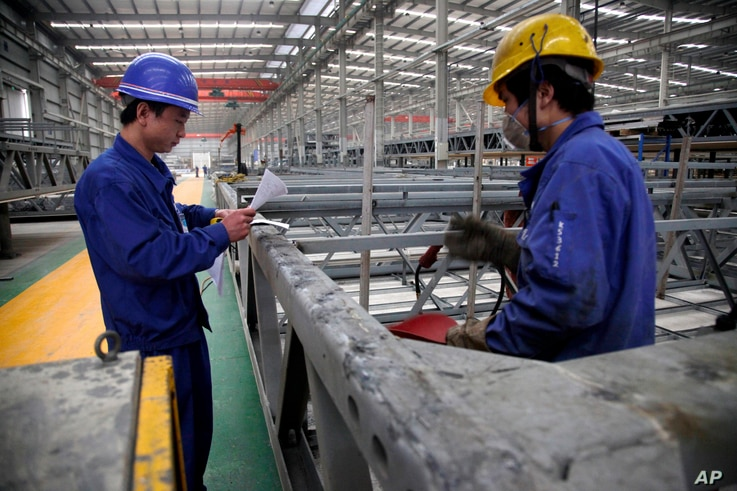 FILE -  workers look over building beams at the Broad Sustainable Building Co. in Yueyang in central China's Hunan Province.