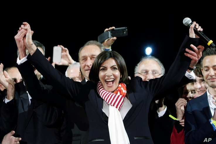 French Socialist Party deputy mayor of Paris, Anne Hidalgo, center, smiles, as outgoing mayor Bertrand Delanoe, stands behind her, during a speech after results were announced in the second round of the French municipal elections, in Paris, Sunday, M...
