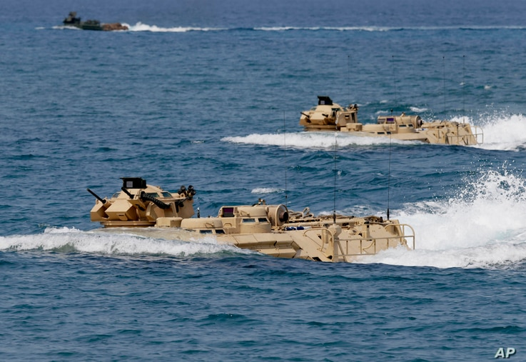 FILE - U.S. Navy amphibious assault vehicles with Philippine and U.S. troops on board are seen during joint exercises near a beach facing one of the contested islands in the South China Sea known as the Scarborough Shoal in the West Philippine Sea, A...