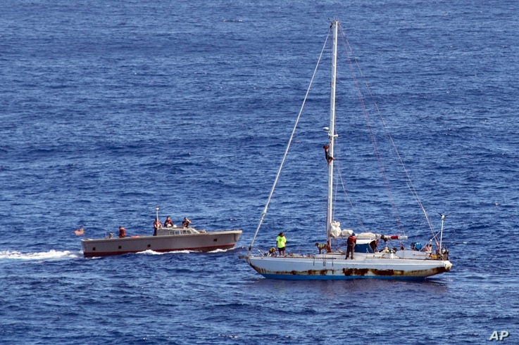 In this Oct. 25, 2017 photo, sailors from the USS Ashland approach a sailboat with two Honolulu women and their dogs aboard as they are rescued after being lost at sea for several months while trying to sail from Hawaii to Tahiti.