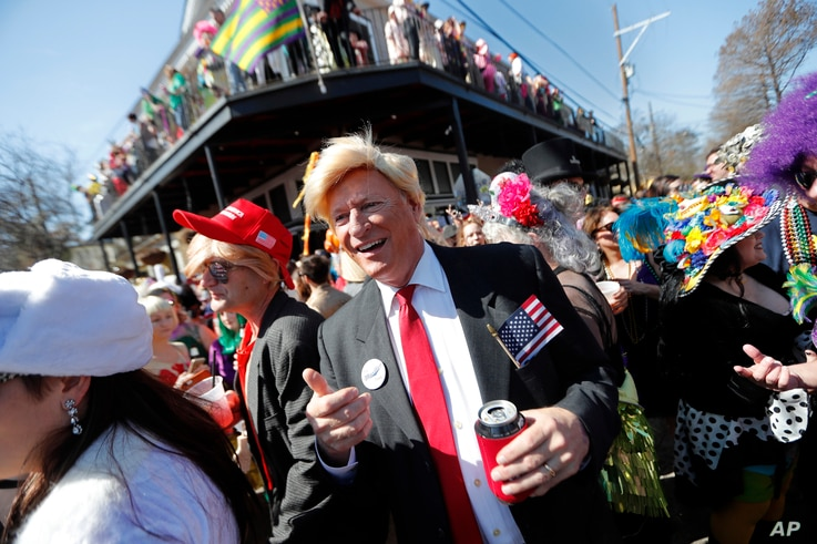 John Shreves, center, of New Orleans, runs into Jeff Jones, right, who both dressed as Donald Trump, during the Society de Sainte Anne parade, on Mardi Gras day in New Orleans, Tuesday, Feb. 13, 2018.