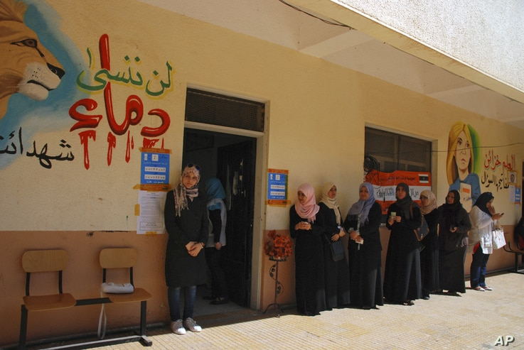 """Libyan voters line up at a polling station in Benghazi, Libya Saturday, July 7, 2012. Jubilant Libyans marked a major step toward democracy after decades of erratic one-man rule by longtime dictator Moammar Gadhafi. Arabic at left reads """"don't forget..."""
