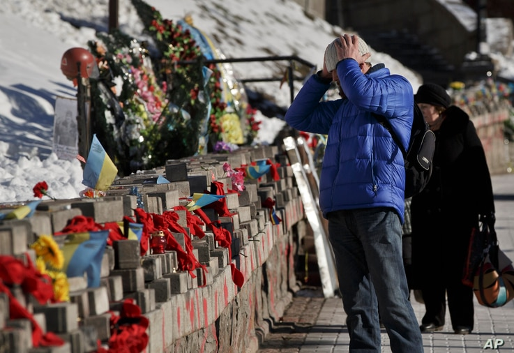 A man looks at pictures of victims of the Maidan Square protests placed in Kyiv, Ukraine, Feb. 17, 2015.