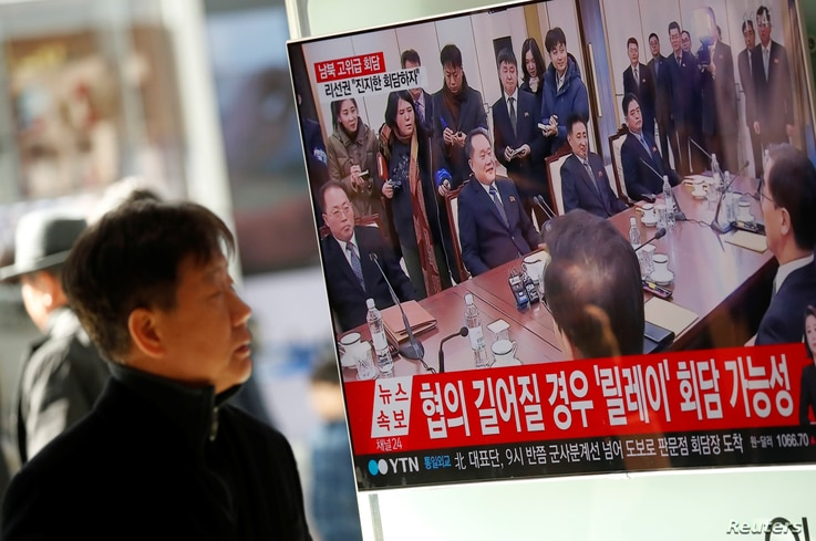 A man watches a TV broadcasting a news report on a high-level talks between the two Koreas at the truce village of Panmunjom, in Seoul, South Korea, Jan. 9, 2018.