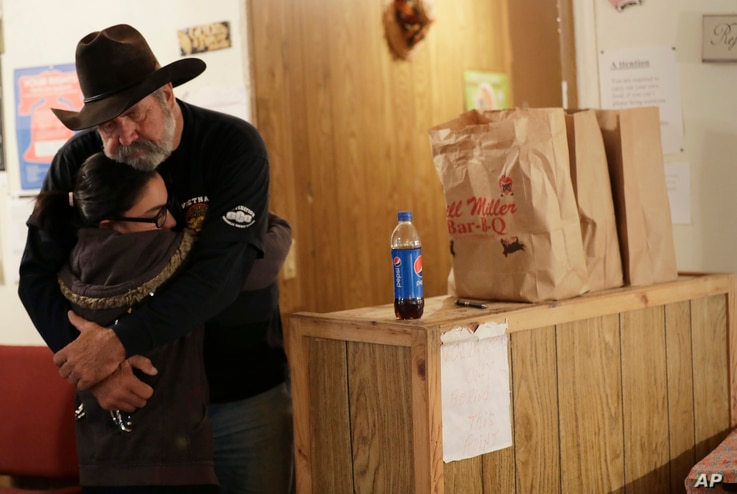 Rod Green, right, hugs a friend at By His Grace, a food pantry affiliated with Sutherland Springs Baptist Church in Sutherland Springs, Texas, Nov. 10, 2017.