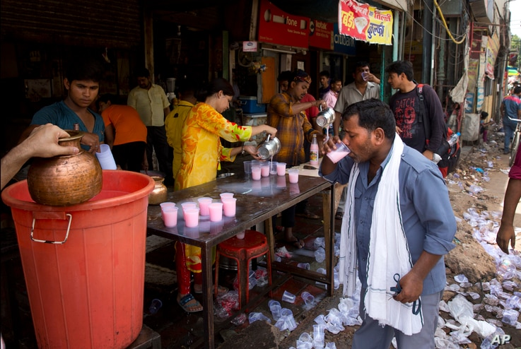 An Indian auto rickshaw driver, right, drinks sweetened water being freely distributed by the wayside on a hot summer afternoon in New Delhi, India, June 5, 2017.