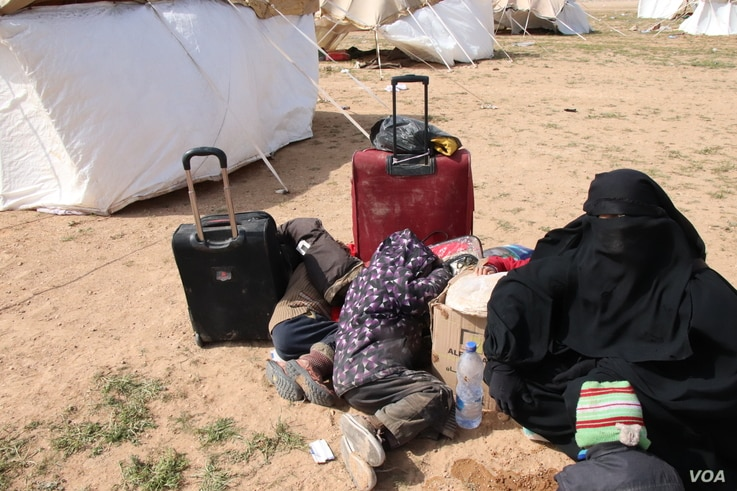 "A woman, not knowing when or where she is going, waits with her children behind a collection of tents. ""I don't know who I'm supposed to be afraid of, but I am afraid,"" she says, near Baghuz in Deir el-Zour, Syria, Feb. 26, 2019. (H.Murdock/VOA)"
