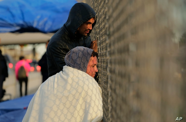 Yenly Herrera, front, and Yenly Morales, immigrants from Cuba seeking asylum in the United States, wait on the  International Bridge, Nov. 2, 2018, in Matamoros, Mexico.