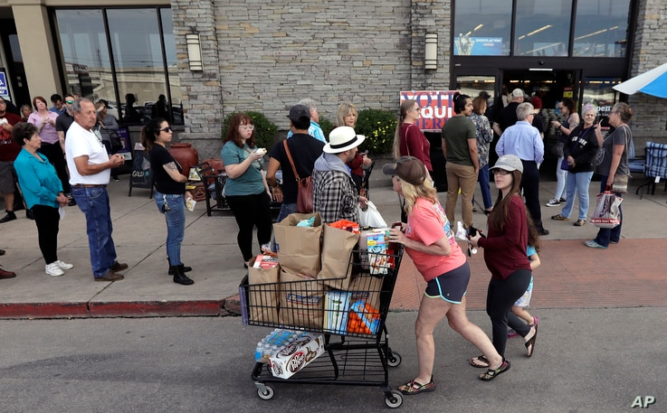 Shoppers pass a line of voters at a grocery store which is also serving as a polling site for the Texas primary elections, in Austin, Texas, March 6, 2018.