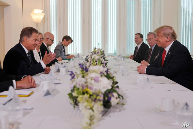 Finnish President Sauli Niinisto, left, and U.S. President Donald Trump, right, sit down for a working breakfast at Niinisto's official residence in Helsinki, Finland, Monday, July 16, 2018.