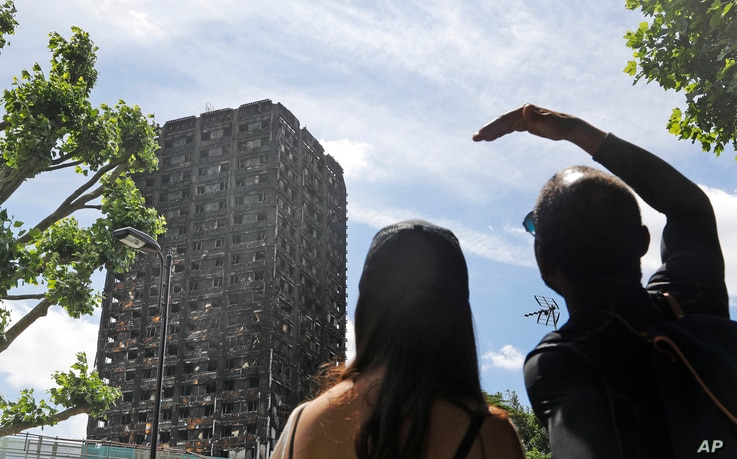 People look at the burned Grenfell Tower apartment building in London, June 23, 2017.  Investigators have traced the source of the June 14 fire to a refrigerator in one of the fourth-floor apartments.