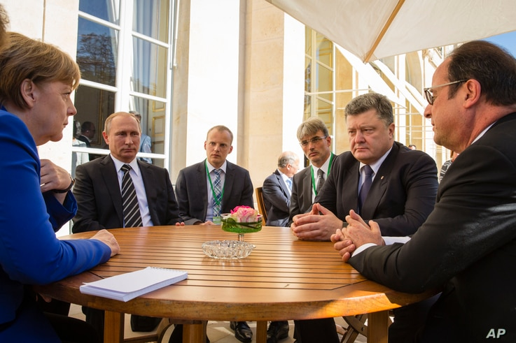 In a revived European push to bring peace to eastern Ukraine, (from left to right), German Chancellor Angela Merkel, Russian President Vladimir Putin, Ukrainian President Petro Poroshenko and French President Francois Hollande take part in an informa...