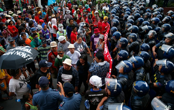 Protesters are blocked by riot police as they march to the U.S. Embassy to denounce the U.S. military's role to quell the two-month-long siege of Marawi city in southern Philippine by Muslim militants Saturday, July 22, 2017 in Manila, Philippines.
