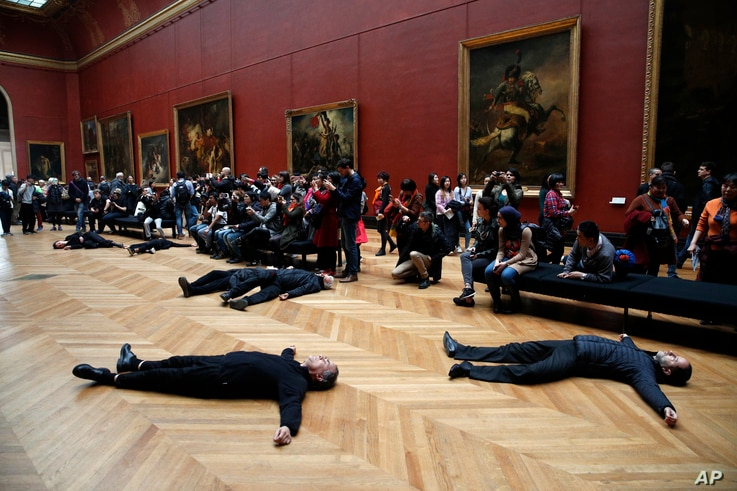 Activists lie on the floor inside the Louvre museum, as they stage a protest trying to call attention to migration driven by climate change, and notably to criticize activities of French oil giant Total, a prominent sponsor of Louvre activities, in P...