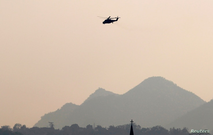 An MI-35M military helicopter flies over Christian church in Lashio, February 19, 2015.