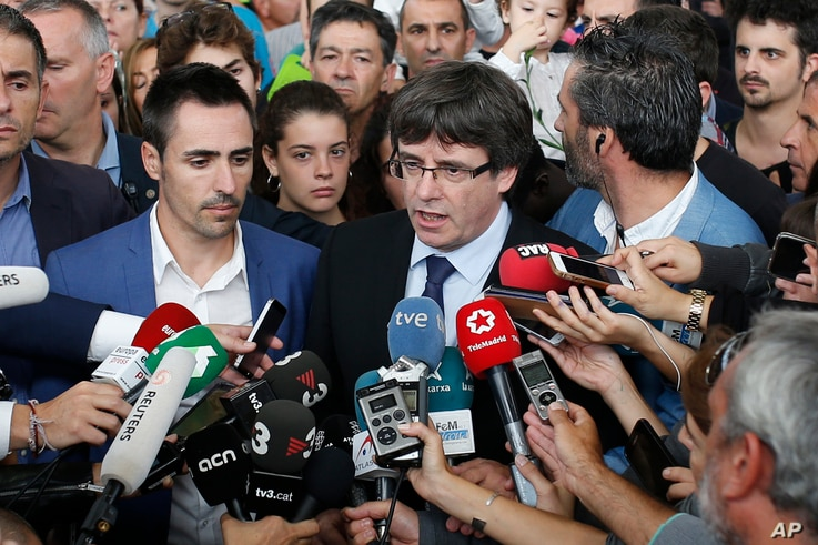 Catalan President Carles Puigdemont, centre, speaks to the media at a sports center, assigned to be a polling station by the Catalan government and where Puigdemont was originally expected to vote, in Sant Julia de Ramis, near Girona, Spain, Oct. 1,