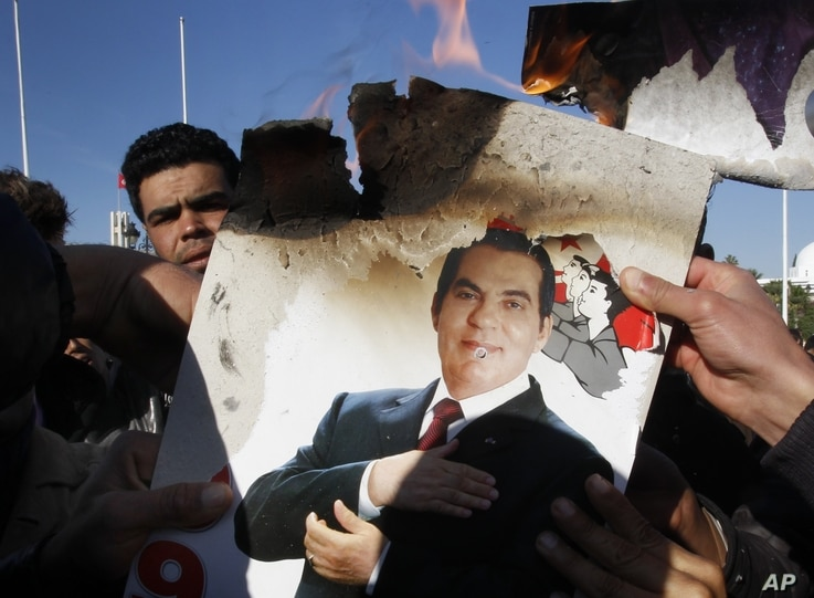 In this Jan. 24, 2011 picture, protestors burn a photo of former Tunisian President Zine El Abidine Ben Ali during a demonstration against holdovers from Ben Ali's regime in the interim government in Tunis, Tunisia.