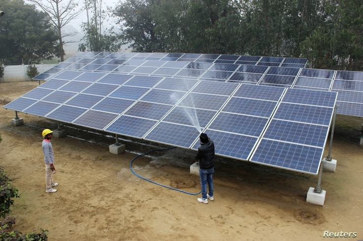 Solar panels are washed at a solar mini-grid installation in Kamlapur, in the Indian state of Uttar Pradesh, Jan. 9, 2018.