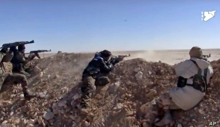 FILE - This frame grab from a video provided by the Syria Democratic Forces (SDF), shows fighters from the SDF opening fire on an Islamic State group's position, in Raqqa's eastern countryside, Syria, March 6, 2017.