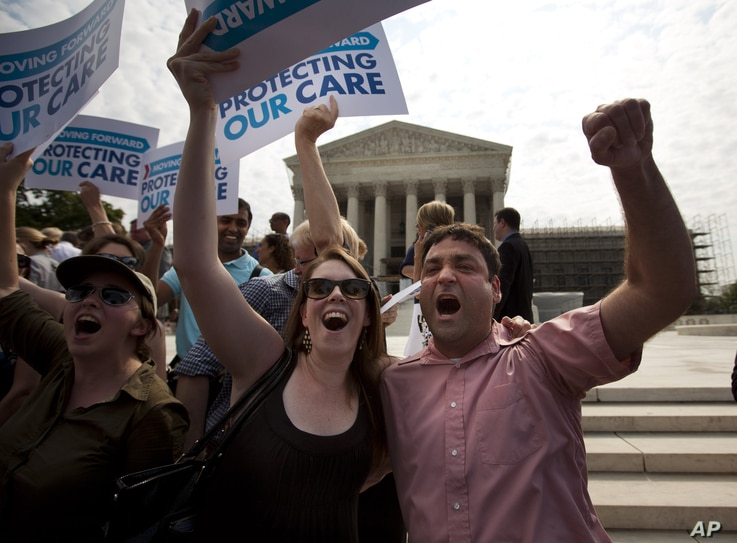 Claire McAndrew of Washington, left, and Donny Kirsch of Washington, celebrate outside the Supreme Court in Washington after the court's ruling on health care.