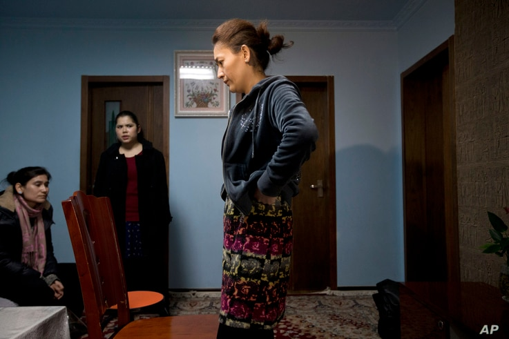 Guzaili Nu'er, wife of Ilham Tohti, right, pauses next to her husband's students at her house in Beijing Thursday, Jan. 16, 2014. Police have taken away Ilham Tohti, an outspoken scholar , seizing computers, cellphones and even his students' theses, ...